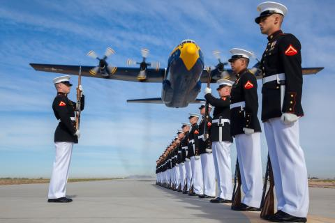A group of Marines in dress uniform perform drill and ceremonies as a C130 airplane passes above them